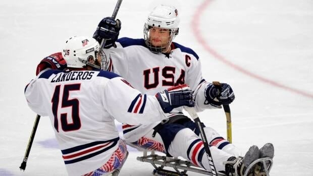 The USA's Taylor Chase, right, celebrates his goal against Canada with Nikko Landeros during the gold medal game of the World Sledge Hockey Challenge in Calgary, Alberta on Saturday, Dec. 8, 2012.