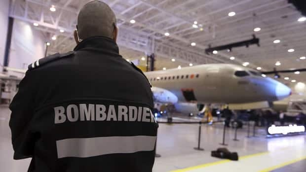 A security guard looks on at an unveiling of Bombardier's CSeries aircraft at an assembly facility in Mirabel, Que., on March 7, 2013. The company said it has completed the last set of safety tests that must be completed before the much-anticipated jet gets Transport Canada approval.
