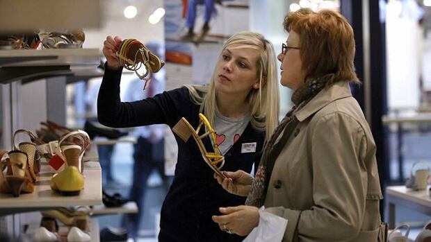 A sales assistant helps a shopper look at shoe prices last month. Canada's service sector expanded by 0.3 per cent in April.