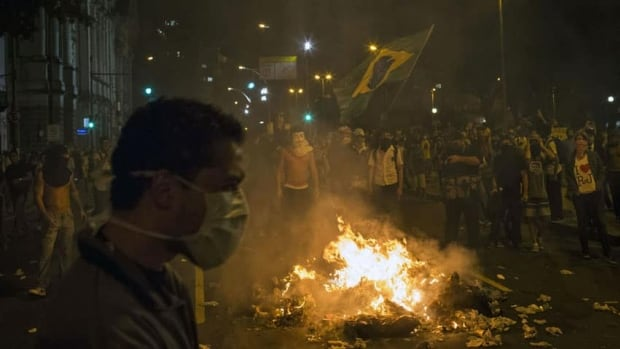 Protesters burn trash to block a street near the sate legislative assembly building during a protest in Rio de Janeiro, Brazil. Tens of thousands of demonstrators marched through the streets of Brazil's biggest cities on Monday.