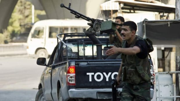 A member of the Free Syrian Army shouts at his comrades to take cover as another fighter prepares to fire at a jet with an anti-aircraft machine gun on Sept. 9.