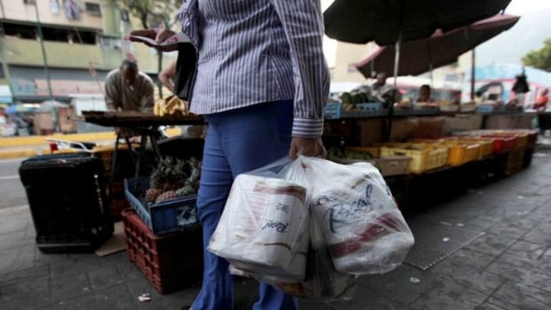 A woman who just bought toilet paper at a grocery store reads her receipt as she leaves the private store in Caracas, Venezuela, on Wednesday.