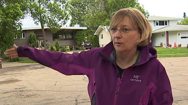 St. Albert resident Terri Lee gestures toward her neighbour's home that has become a boarding house for two dozen construction workers.