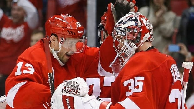 Pavel Datsyuk celebrates with Red Wings goalie Jimmy Howard after Thursday's win over Nashville. Detroit is clinging to a playoff position with Saturday's game at Dallas remaining.
