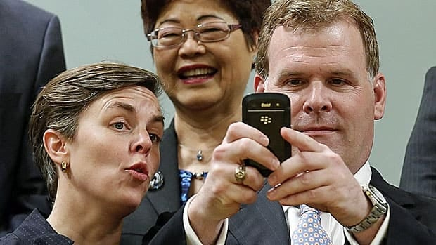 The smartphone cabinet? Foreign Minister John Baird takes a photo of photographers while the new minister of labour, Kellie Leitch, and minister of state for seniors, Alice Wong, look on.