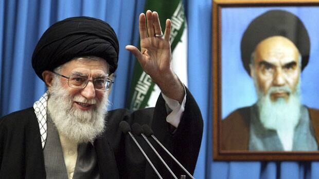 Iranian supreme leader Ayatollah Ali Khamenei waves to the worshippers, in front of a portrait of the late revolutionary founder Ayatollah Khomeini at the Tehran University campus.