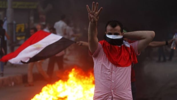 A supporter of ousted Egyptian President Morsi makes the Rabaa or Four gesture during clashes in Cairo. Morsi supporters have used the symbol to remember the Cairo sit-in at the Rabaah al-Adawiya mosque, which in Arabic means fourth.