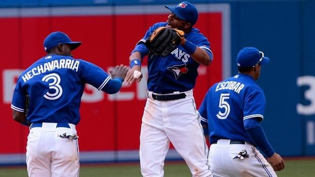 Adeiny Hechavarria (3), Rajai Davis (11) and Yunel Escobar (5) of the Toronto Blue Jays celebrate the win against the New York Yankees during MLB action at the Rogers Centre in Toronto.
