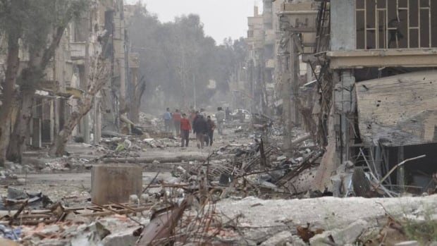 Streets in Deir Al-Zor damaged by a Syrian Air Force fighter jet are shown on Tuesday. Fighting raged Wednesday in Homs and the capital, Damascus.