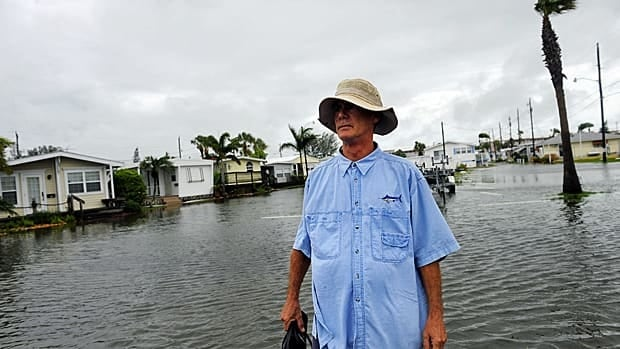 Sean Kummerow, from Bradenton Beach, Fla., walks out to the seawall behind his flooded neighborhood on Monday to inspect damage and look for waterspouts, as a storm surge and high winds associated with tropical storm Debby batter the area.