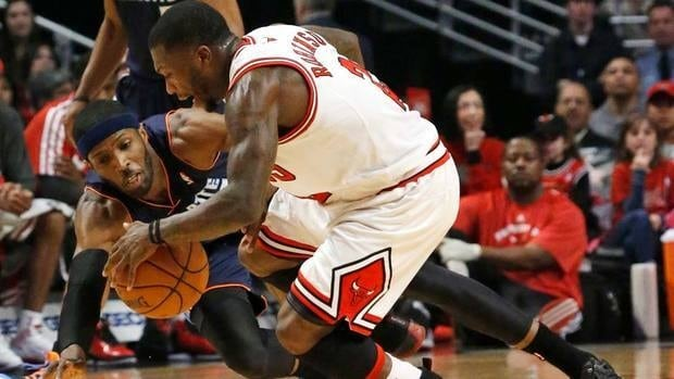 Chicago Bulls guard Nate Robinson works against Charlotte Bobcats forward Hakim Warrick for a loose ball during the first half of their Monday game. Bobcats won for the first time in 19 games.