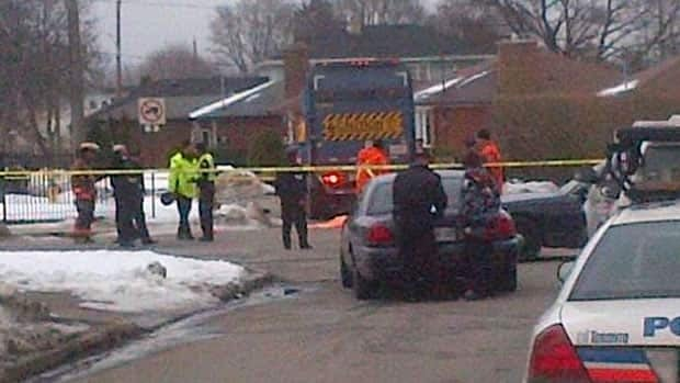 Police investigate at the scene where a five-year-old was killed after being struck by a garbage truck.