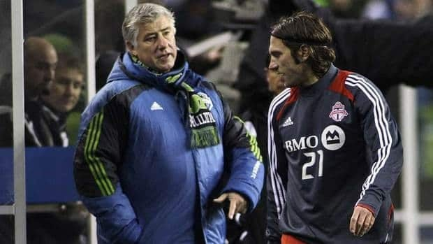 Seattle Sounders coach Sigi Schmid, left, talks to Toronto FC's Torsten Frings as Frings leaves Saturday's soccer match in the first half with a hamstring injury. The Sounders won 3-1.