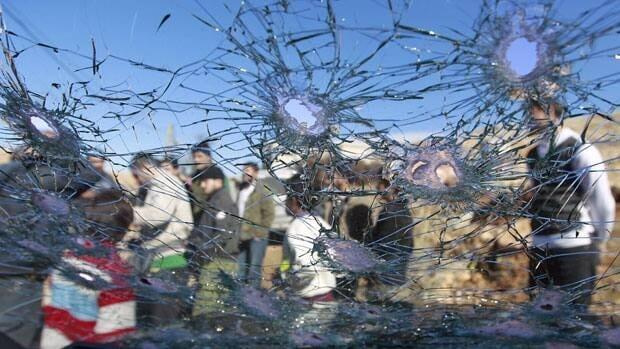 Lebanese civilians are seen through a bullet riddled car window, in Arsal, a Sunni Muslim town eastern Lebanon near the Syrian border, Saturday, Feb. 2, 2013.