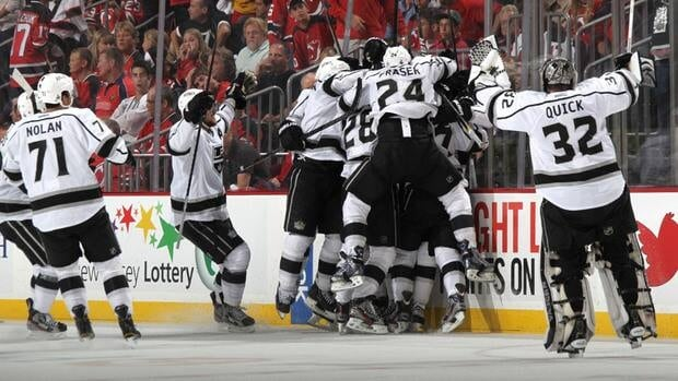 The Los Angeles Kings celebrate around Jeff Carter (7) after he scored the game winning goal in overtime against the New Jersey Devils in Game 2 on Saturday.