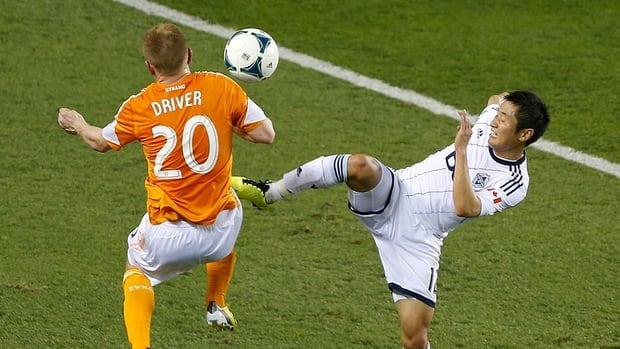 Young-Pyo Lee of the Vancouver Whitecaps, right, battles for the ball with Andrew Driver of the Houston Dynamo.