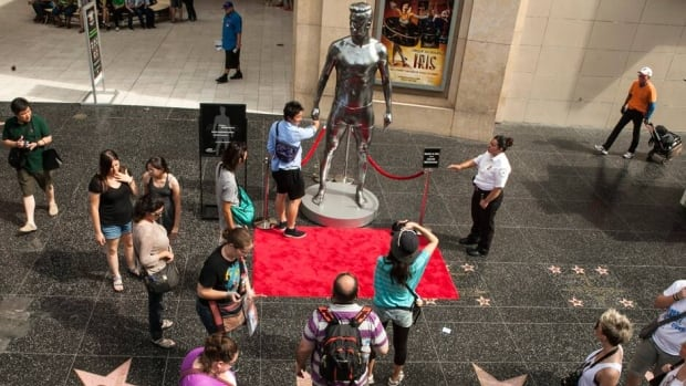 Tourists gawk at a David Beckham statue in Hollywood, Calif.