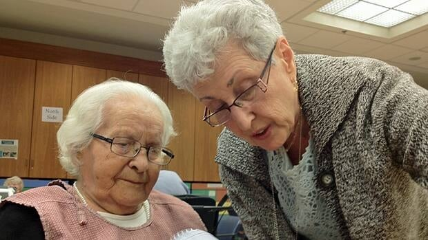 Volunteer Edith Shoom (standing) assists long-term care resident Ester Cynamon to dry her art project at Baycrest Health Sciences in Toronto. Shoom said volunteering gives her a sense of accomplishment and well-being.