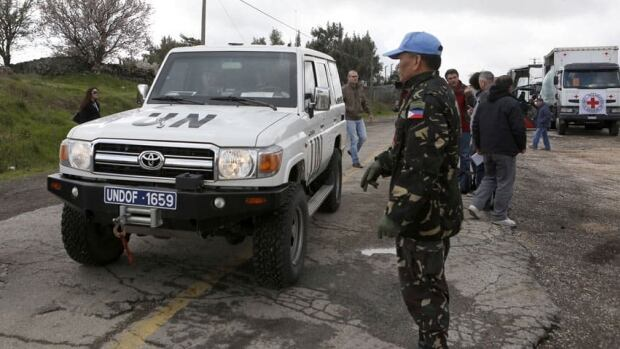 A Filipino United Nations peacekeeper stands next to a UN vehicle before it crosses from Israel into Syria at the Kuneitra border crossing on the Golan Heights March 5, 2013. Syrian rebels have seized a convoy of UN peacekeepers near the Golan Heights.