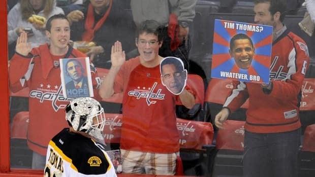 Boston Bruins goalie Tim Thomas (30) skates during warm-ups as fans hold signs before Game 3 on Monday in Washington.