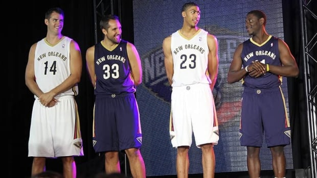 Jason Smith (14), Ryan Anderson (33), Anthony Davis (23) and Jrue Holiday (11) of the New Orleans Pelicans model during a press conference to showcase the team's new uniform on Thursday.