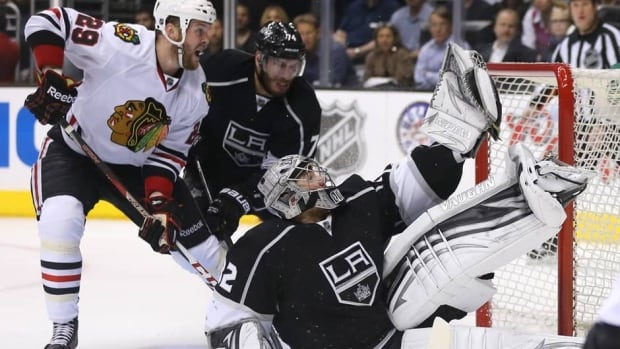 Goaltender Jonathan Quick (32) of the Los Angeles Kings makes a glove save on a shot by Patrick Kane (88) of the Chicago Blackhawks, not pictures, as Chicago's Bryan Bickell (29) battles with L.A.'s Dwight King (74) in Game 4 on Thursday.