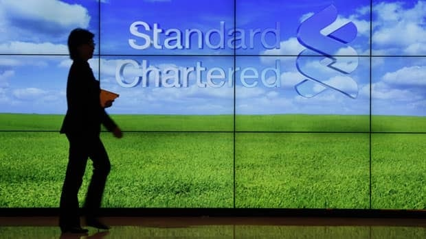 A staff member walks inside a priority banking service area of a Standard Chartered bank in Hong Kong on August 1, 2012.
