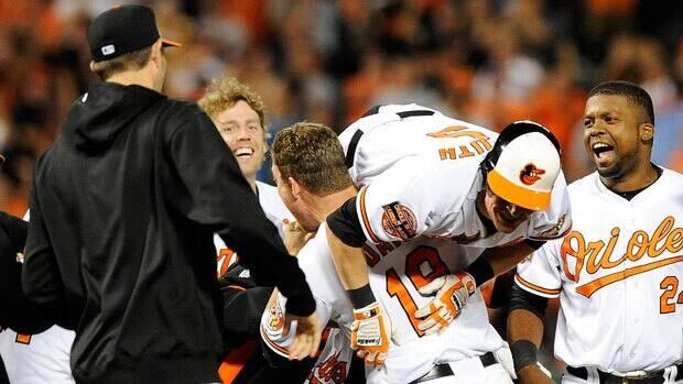 Baltimore's Chris Davis picks up teammate Nate McLouth after McLouth's game-winning RBI in the ninth inning.