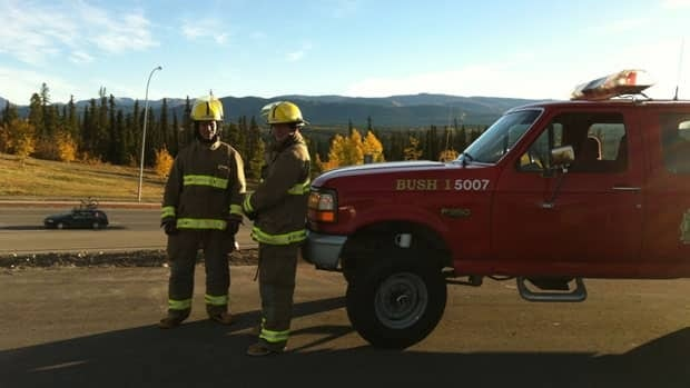 Whitehorse firefighters stand outside their station on Two Mile Hill Thursday morning to let people know to report emergencies directly to them while 911 service was down.