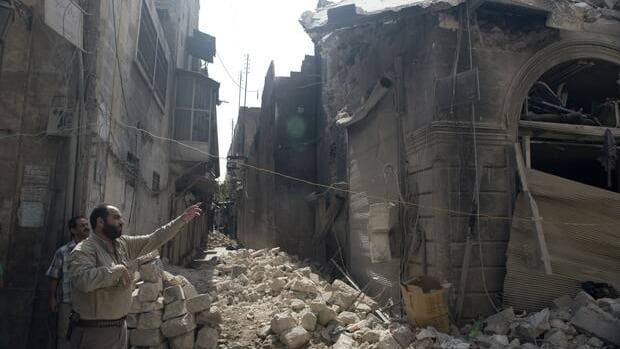 Syrians inspect damages in the old city of Aleppo after shelling by Syrian regime forces on Sept. 30. Regime forces bombarded a city in the northwest Monday, killing at least 21, activists say.