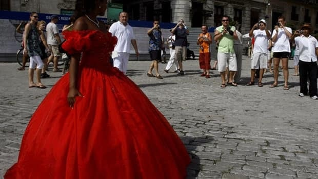 A young woman celebrating her 15th birthday posses for tourists in Old Havana, Cuba. The country has an outbreak of cholera that prompted Canadian and European health agencies to issue health advisories for travellers.