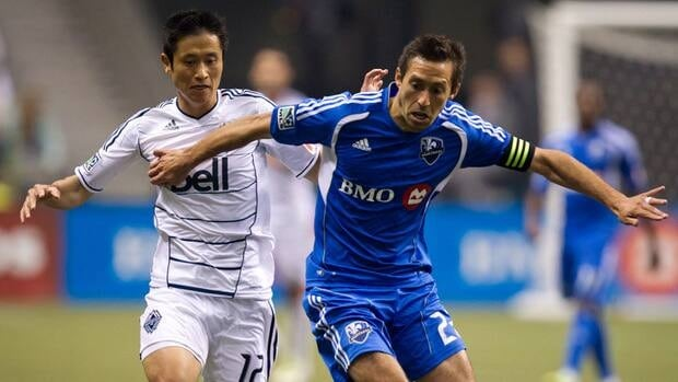Vancouver Whitecaps' Young-Pyo Lee, left, and Montreal Impact's Davy Arnaud during a game in Vancouver, B.C., on Saturday March 10, 2012.