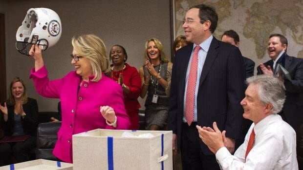 U.S. Secretary of State Hillary Rodham Clinton holds up a football helmet presented to her at the State Department in Washington, on Monday.