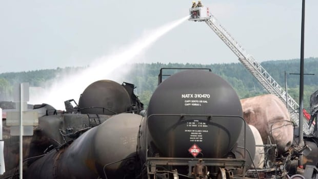 Fire fighters keep watering railway cars the day after a train derailed causing explosions of railway cars carrying crude oil on Sunday in Lac-Mégantic, Que.