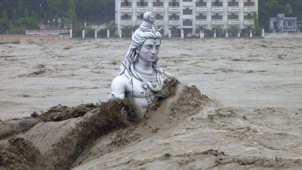 Flooding in mid-June swamps a statue of the Hindu diety Shiva. The floods killed more than 5,700 people.