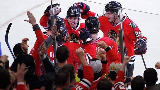 Chicago Blackhawks players including Patrick Kane, Brandon Saad, Duncan Keith and Niklas Hjalmarsson surround Jonathan Toews (lower left) after Toews scored the eventual game winner in the third period against Nashville on Sunday.