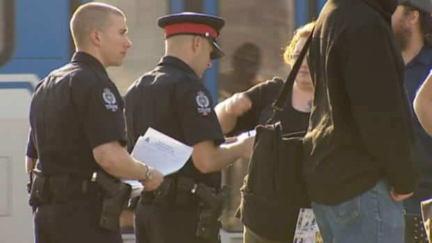 Police talk to witnesses to stabbings near the Kingsway Transit Centre on Saturday evening.