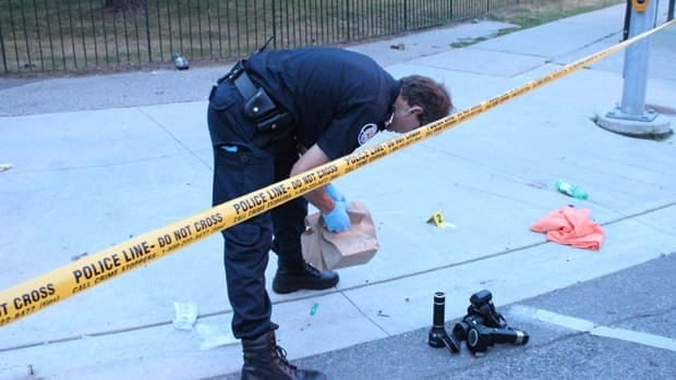 A member of the forensics team searches for evidence on Danzig Street.