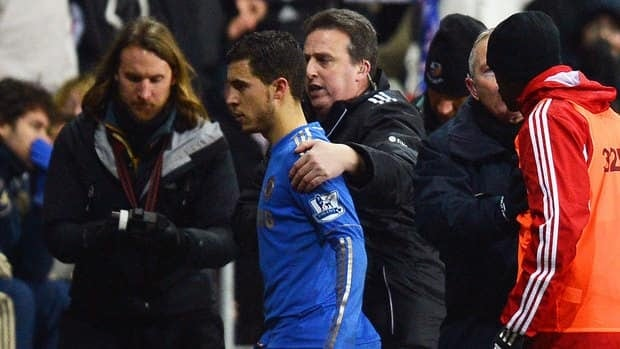 Chelsea's midfielder Eden Hazard, centre, is escorted off the pitch after being ejected for a kicking incident with a ball boy Wednesday against Swansea.