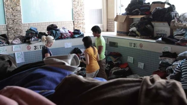 Volunteers sort through donated clothes in the drained swimming pool of a Calgary emergency shelter which used to be a hotel.