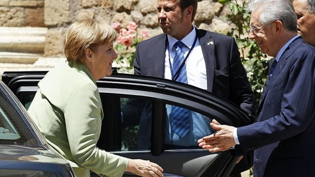 German Chancellor Angela Merkel (left) is welcomed by Italian Prime Minister Mario Monti (right) as she arrives for a meeting at Villa Madama in Rome on Friday.