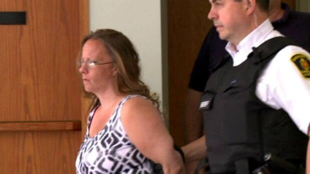 Wanda Ash is escorted from provincial court in Grand Falls-Windsor.