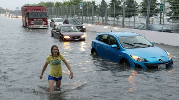 A woman wades through flood water on Lakeshore West during a storm in Toronto on Monday, July 8, 2013. The flood disrupted the evening commute for many, including a number of northbound passengers who were stuck on a GO train for hours.