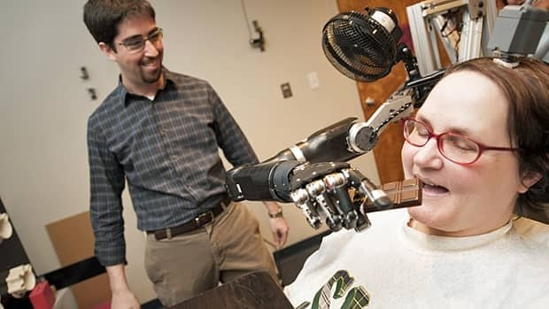Jan Scheuermann, who has quadriplegia, takes a bite out of a chocolate bar she has guided into her mouth with a thought-controlled robotic arm, as research assistant Brian Wodlinger looks on.