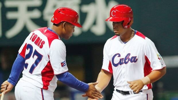 Cuba's first baseman Jose Abreu, right, is welcomed by teammate Tomas Yasman at home after hitting a grand slam off China's Liu Yu in the fifth inning in Fukuoka, Japan.
