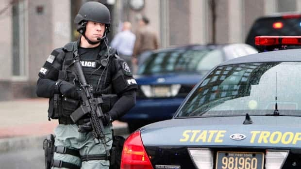 An officer with a assault rifle takes up a postion outside the New Castle County Courthouse in Wilmington after the shooting inside the building.