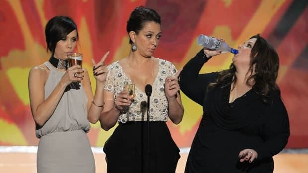 "Kristen Wiig, left, Maya Rudolph, centre, and Melissa McCarthy play a ""Scorsese drinking game"" while introducing a clip from their film Bridesmaids at the 18th annual Screen Actors Guild Awards in Los Angeles last month. A British study suggests such films featuring alcohol are linked to teen drinking."