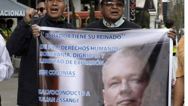 Men hold up a sign with an image of WikiLeaks founder Julian Assange that reads in Spanish that Ecuador has its kingdom of peace, human rights, sovereignty, dignity and freedom of expression, during a demonstration in support of the asylum granted by Ecuador to Assange in Quito.