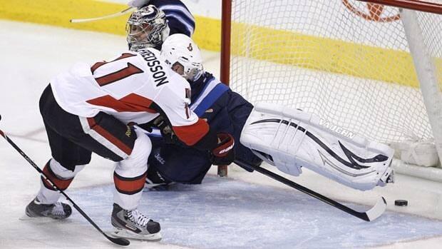 The Ottawa Senators' Daniel Alfredsson puts the puck past Winnipeg Jets' goalie Ondrej Pavelec. Alfredsson is among 22 NHL players heading North to play charity games.