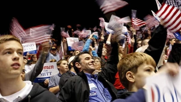People wave the American flag as Republican presidential candidate Mitt Romney speaks during a campaign event at The Patriot Center at George Mason University in Fairfax, Va.